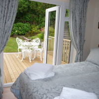 Compact double room with patio doors opening out to decking and enclosed garden beyond